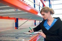 女实业家文字的画象在剪贴板的在仓库里 免版税图库摄影