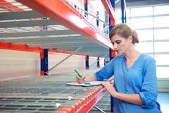 女实业家在架子的文字存货在仓库里 免版税库存照片