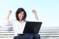 有膝上型计算机的欣快女实业家坐长凳 免版税图库摄影
