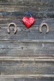 两在木墙壁上的生锈的马掌和心脏标志 库存照片