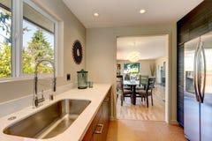 有大水槽和白色工作台面的现代小新的厨房。 库存图片