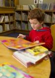 读一本书的男孩在图书馆里 图库摄影