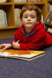 地板阅读书的男孩 免版税库存照片