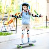 有盔甲骑马的小女孩在滑板 免版税图库摄影