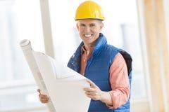 拿着图纸的愉快的建筑工人在站点 免版税库存图片