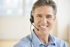 Αρσενική αντιπροσωπευτική φορώντας κάσκα εξυπηρέτησης πελατών Στοκ Εικόνες