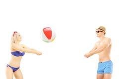 年轻男性和女性使用与海滩球的游泳衣的 图库摄影