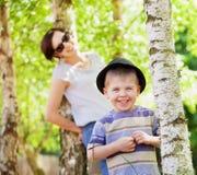 微笑的孩子和他的妈妈在背景中 免版税库存照片