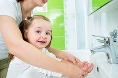 母亲洗涤的孩子手 免版税库存照片