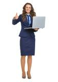 有显示赞许的膝上型计算机的微笑的女商人 免版税库存照片