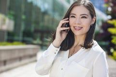 亚裔妇女或女实业家谈话在手机 免版税库存图片