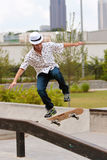 Человек практикует фокус скейтборда на перилах Стоковые Фото