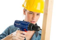 Рабочий-строитель используя бесшнуровое сверло на деревянной планке Стоковое Изображение
