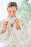 妇女嗅到的咖啡在健康温泉的 免版税库存照片