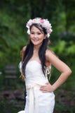 美丽的亚裔夫人白色新娘礼服,摆在森林里 免版税库存照片