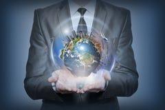 行星地球在蓝色背景的人的手上 免版税图库摄影