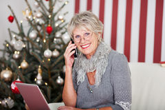 聊天在电话的资深妇女在圣诞节 免版税库存照片