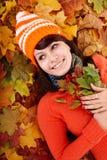 秋天橙色叶子的少妇。 免版税库存照片