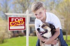 年轻男孩和他的狗在卖前面为销售标志和议院 图库摄影