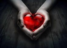 玻璃心脏在心脏手上 免版税库存照片