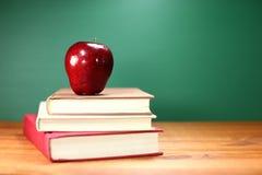 回到教科书和苹果计算机与黑板 免版税库存照片