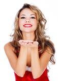 Милая молодая женщина в красном платье дуя поцелуй на вас Стоковые Изображения