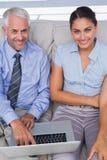 使用在长沙发的商人膝上型计算机和微笑在来了 免版税库存图片