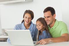 使用一台膝上型计算机的家庭在厨房用桌上 免版税库存照片