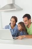 使用一台膝上型计算机个人计算机的家庭在厨房用桌上 免版税图库摄影