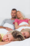 睡觉在他们的父母前面的床上的孪生 库存照片