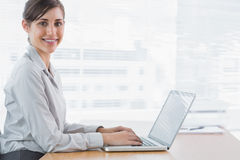 键入在她的膝上型计算机在书桌和微笑对照相机的女实业家 免版税图库摄影