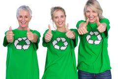 Τρεις γυναίκες που φορούν το πράσινο δόσιμο μπλουζών ανακύκλωσης φυλλομετρούν επάνω Στοκ φωτογραφία με δικαίωμα ελεύθερης χρήσης