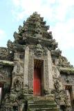 古老巴厘语雕刻了与红色门的石寺庙入口 库存图片