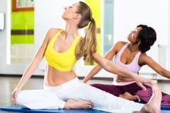 做瑜伽的健身房的妇女为健身行使 免版税库存图片
