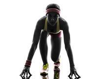 运行在出发台剪影的妇女赛跑者 免版税图库摄影