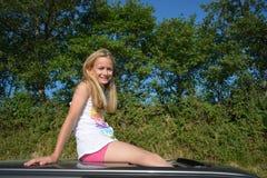 愉快的女孩坐汽车屋顶 免版税库存照片