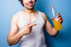 年轻在一种满身是汗的锻炼以后的人饮用的能量饮料 库存图片