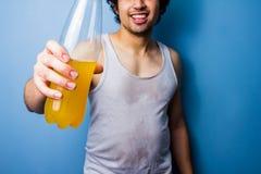 年轻在一种满身是汗的锻炼以后的人饮用的能量饮料 免版税库存照片