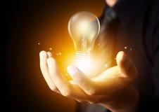电灯泡在人手上 库存图片