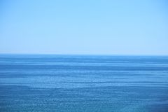 风平浪静和蓝色清楚的天空 库存图片