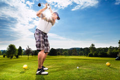 做高尔夫球摇摆的路线的年轻高尔夫球运动员 库存图片