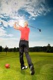 做高尔夫球摇摆的路线的年轻高尔夫球运动员 免版税库存图片