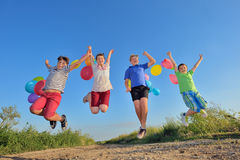 跳跃在与气球的领域的愉快的孩子 免版税库存图片