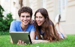 使用数字式片剂的夫妇在草坪 免版税库存图片