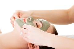在温泉沙龙的秀丽治疗。有面部黏土面具的妇女。 图库摄影