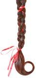 妇女编辫子用在白色隔绝的一把红色弓装饰。 图库摄影