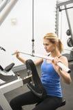 做在健身俱乐部的妇女重量锻炼 库存照片