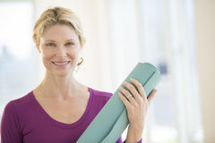 Βέβαια γυναίκα με το χαλί άσκησης που χαμογελά στη γυμναστική Στοκ Εικόνες