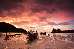被淹没的岩石和长尾巴小船在日落 免版税库存图片