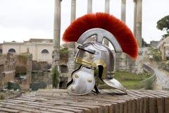 在古老罗马废墟前面的罗马战士盔甲。 库存照片